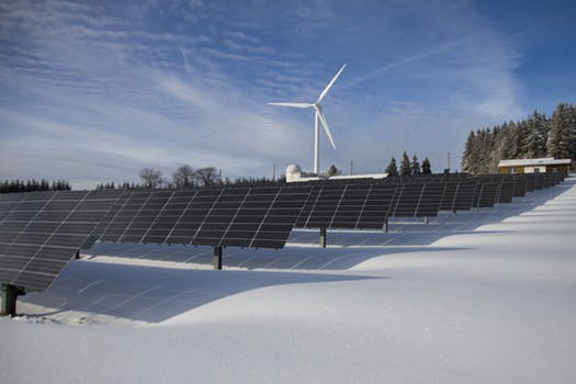 Solar panels in Scotland near snow and a windmill